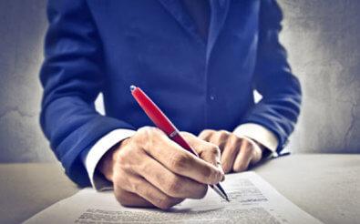 Человек подписывает договор.